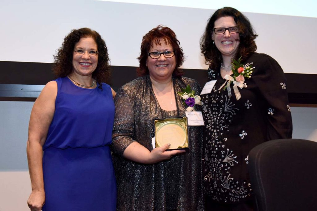 Three women hold awards